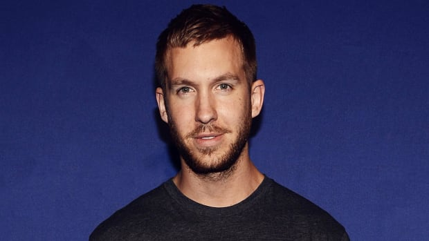 A color press head shot of Scottish DJ/producer Calvin Harris in front of a dark blue background.