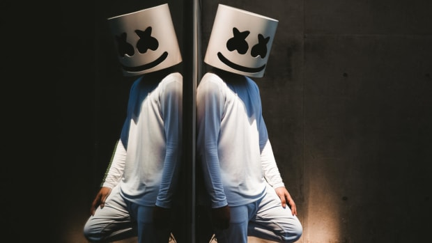 Press photo of Marshmello leaning on a reflective surface.