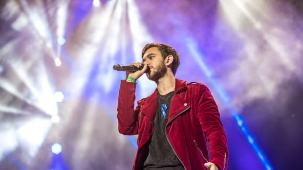 A color photo of German DJ/producer Zedd (real name Anton Zaslavski) on the mic during a performance with spotlights in the background.