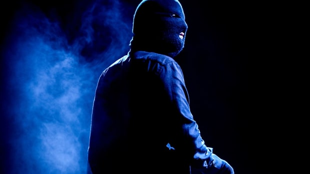 A photo of masked, anonymous DJ/producer Malaa during a performance with smoke in the background.