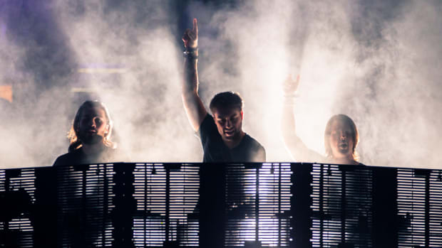 Swedish House Mafia performing with fog around them.