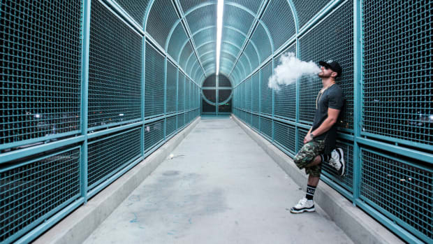 Photo of Los Angeles DJ/producer Lucchii smoking on a bridge.