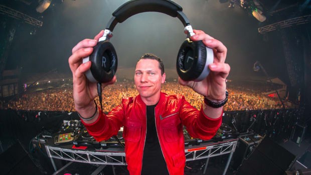 Tiesto holding headphones and wearing a red jacket while DJing in front of a big crowd.