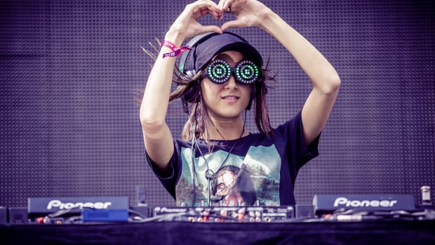 Canadian DJ/producer Rezz giving her audience heart hands behind the decks during a performance.