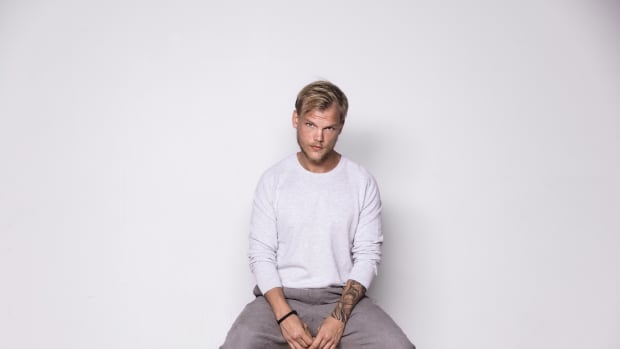 Swedish superstar DJ/producer Avicii in press photo sitting in front of a white backdrop.