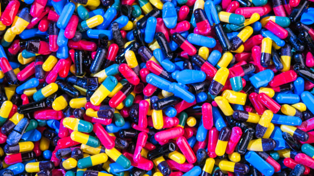 A photo of yellow, blue and pink drug capsules taken by Joshua Coleman.