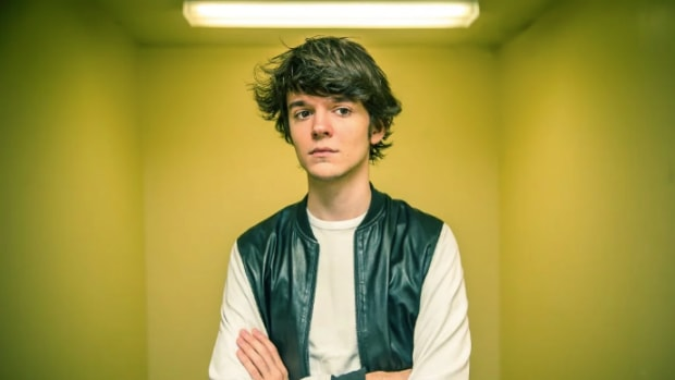 A photo of DJ/producer Madeon (real name Hugo Pierre Leclercq) standing in a room with yellow walls courtesy of Rukes.