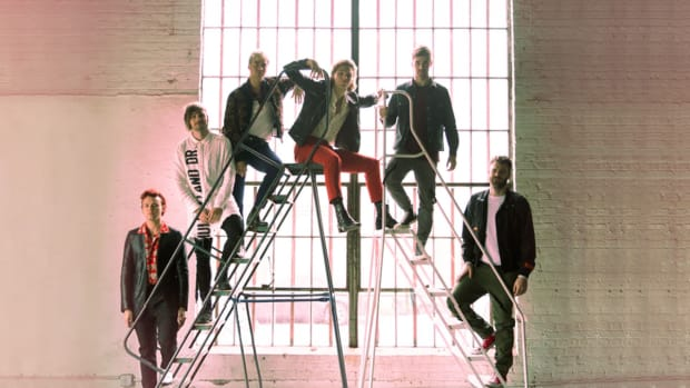 An image of The Chainsmokers and 5SOS on a ladder in front of a window.