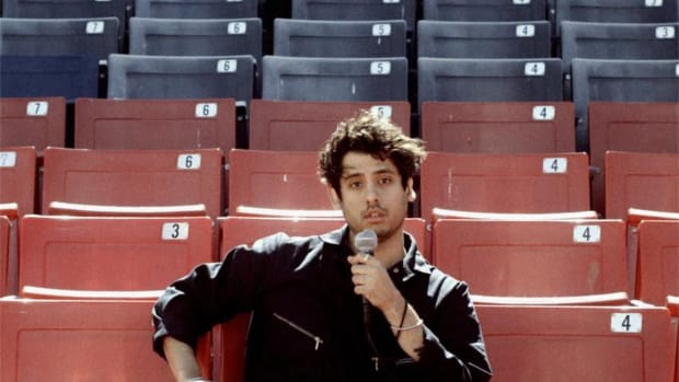 A photo of Ookay sitting in numbered red and blue bleachers holding a dented microphone.