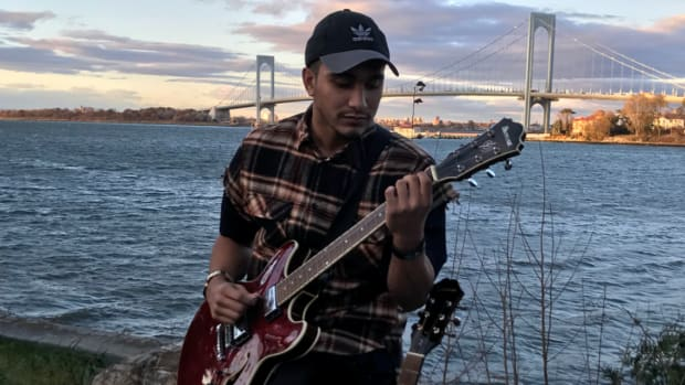 Spce CadeX Holding Guitar With Bridge Crossing the Bay In Background (Press Photo)