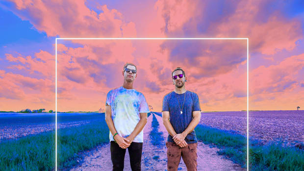 A color photo of Big Gigantic (real names Dominic Lalli and Jeremy Salken) standing on a dirt road in front of a sunset.