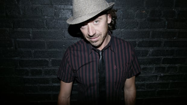 Benny Benassi standing in front of a black brick wall wearing a fedora.