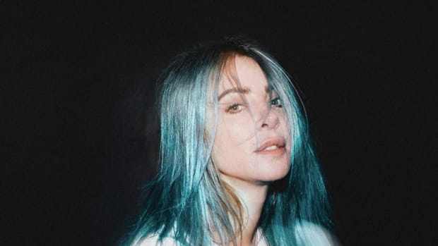 A head shot of Alison Wonderland with dyed blue hair wearing a white tee shirt over a black background.