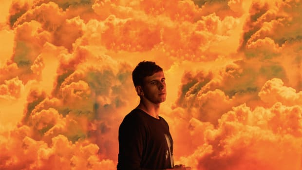 Denver EDM DJ/producer Illenium (real name Nicholas D. Miller) standing in front of orange clouds.