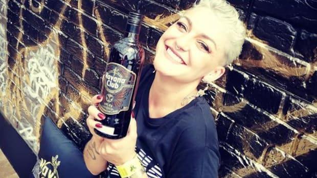 A blonde girl holding Tomorrowland Havana Club TML XV rum.