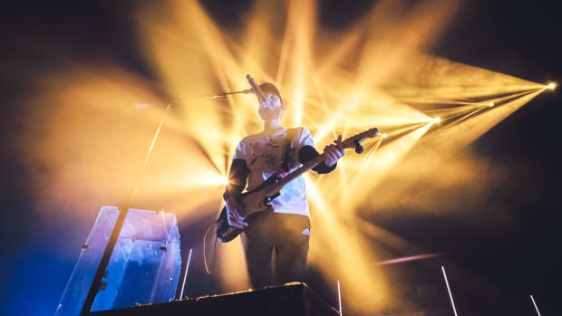 san holo sings into microphone with guitar and yellow lights