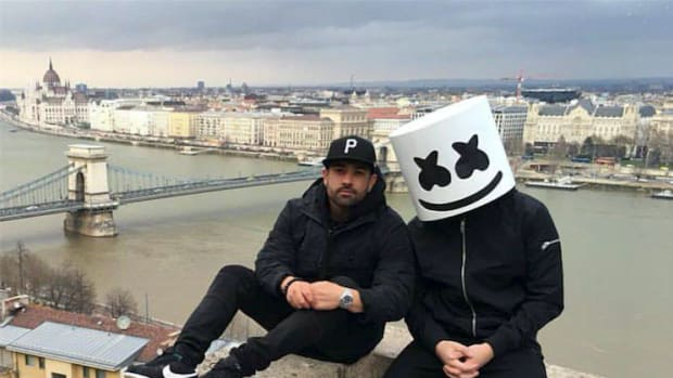 Moe Shalizi sitting on a ledge with Marshmello overlooking a scenic view.