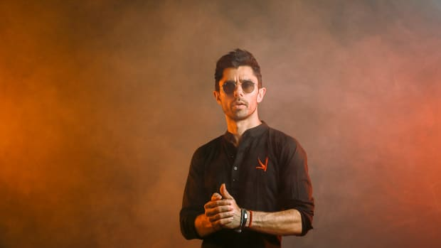 DJ/producer KSHMR over a reddish background.