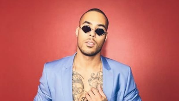 Troyboi in a blue suit in front of a red background.