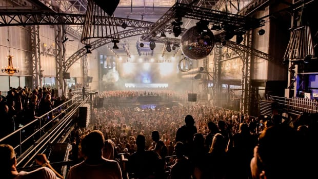 Privilege Ibiza crowd shot with disco ball and attendees in the foreground.