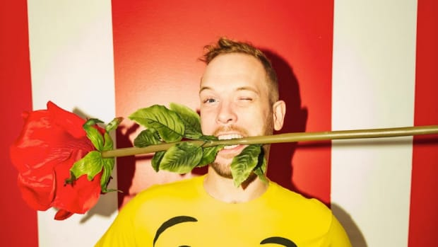 U.K. DJ/producer Rusko A.K.A. Christopher Mercer with a giant fake rose in his mouth in front of a red and white striped background.
