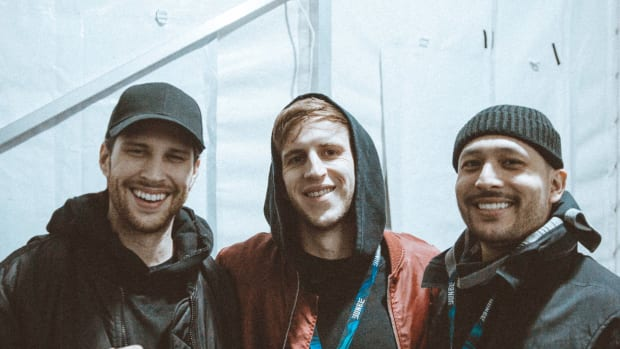 A photo of EDM DJ/producer Illenium with DJ/producer duo SLANDER on either side of him.