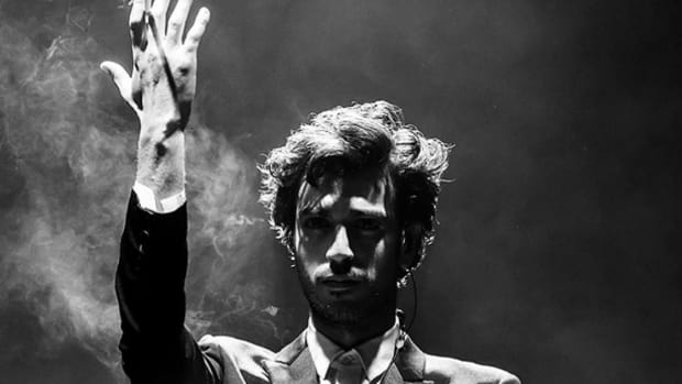 Black-and-white photo of Gesaffelstein with smoke in the background.