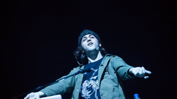 DJ/producer Porter Robinson with his hand extended during a performance.