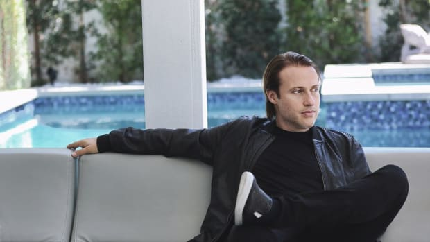 A press photo of Swiss DJ/producer EDX A.K.A. Maurizio Colella sitting on a couch by a pool.