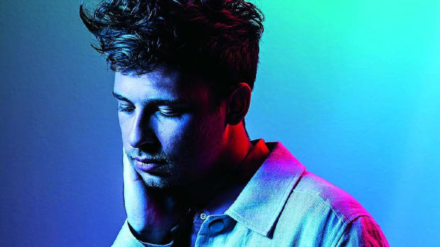A press photo head shot of Flume A.K.A. Harley Edward Streten with blue, turquoise and red lighting.