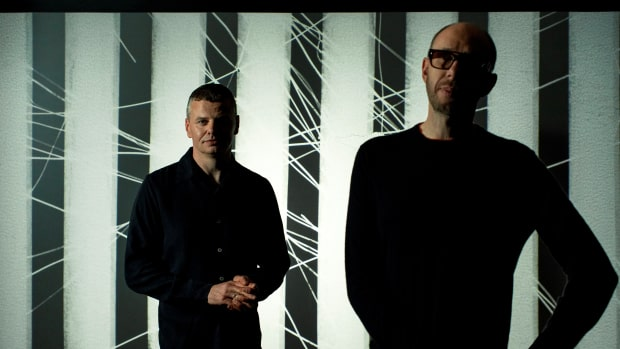 A color press photo of English electronic music duo The Chemical Brothers A.K.A. Tom Rowlands and Ed Simons standing in front of a black-and-white pattern.