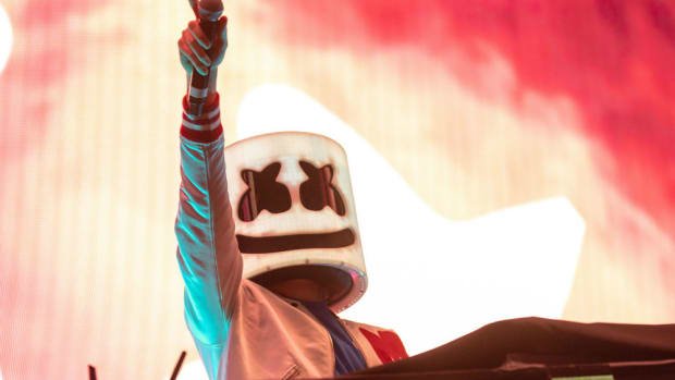 A photo of DJ/producer Marshmello (real name Christopher Comstock) pointing with a mic in his hand during a performance.