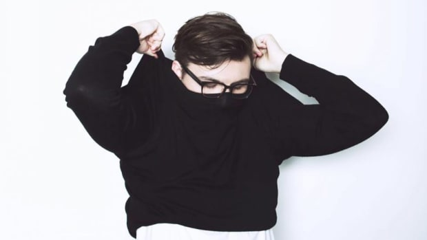 A color press photo of DJ/producer Vincent taking off a black shirt over a white background.