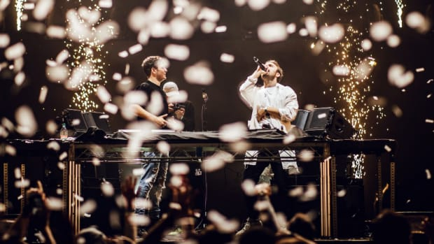 A photo of DJ/producer Martin Garrix and vocalist Bonn onstage while pyrotechnics fire off with sparks in the foreground and background.