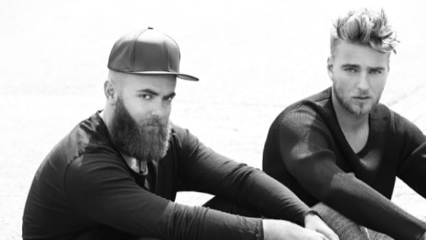 A black and white photo of Dutch DJ/producer duo Showtek (real names Wouter and Sjoerd Janssen) sitting down.