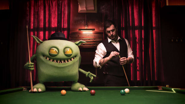 A computer graphics (CG) image of Feed Me (real name Jon Gooch) playing pool with his monster mascot.
