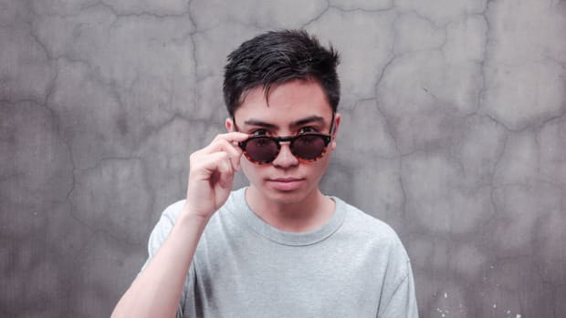 A color press photo of DJ/producer Manila Killa (real name Chris Gavino) lowering his sunglasses so his eyes are visible.