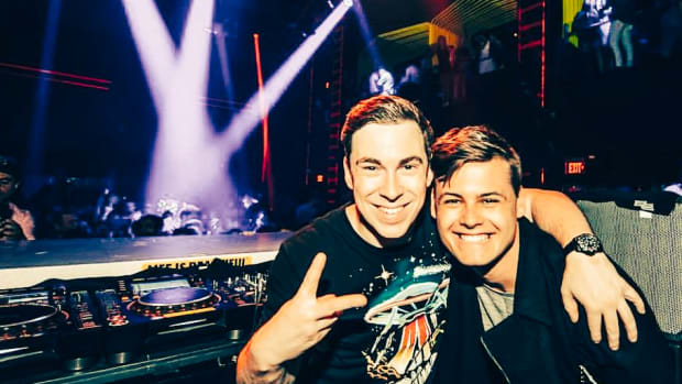 A photo of Dutch DJ/producers Hardwell and Mike Williams behind the decks at a nightclub with spotlights shining on a crowd in the background.