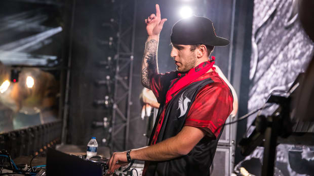 A photo of Denver DJ/producer Illenium with his hand up during a performance.
