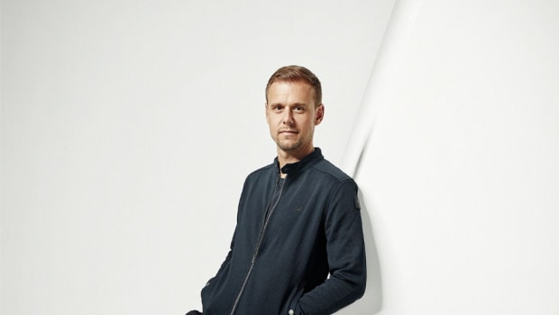 A photo of Dutch DJ/producer Armin van Buuren leaning againsta large letter A.