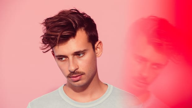 A photo of Australian DJ/producer Flume (real name Harley Edward Streten) in front of a reddish-peach background with a hazy reflection of his face.
