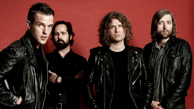 The Killers wearing black leather jackets in front of a red background.
