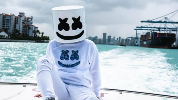Anonymous, masked DJ/producer Marshmello (real name Chris Comstock) sitting by a pool.