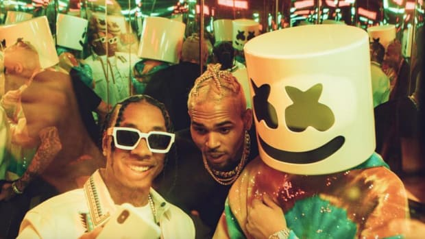A photo of Marshmello, Tyga and Chris Brown standing in a mirrored corner.