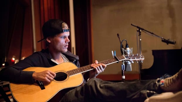 Avicii (real name Tim Bergling) playing an acoustic guitar with studio equipment in the background.