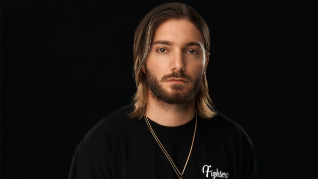Alesso over a black background wearing a gold chain with his logo.