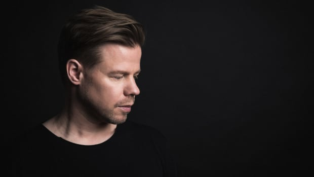 A 2019 color press photo of Dutch DJ/producer Ferry Corsten over a black background.