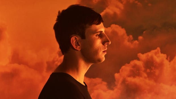 A color press photo of Denver DJ/producer Illenium in a profile pose against orange-red clouds.