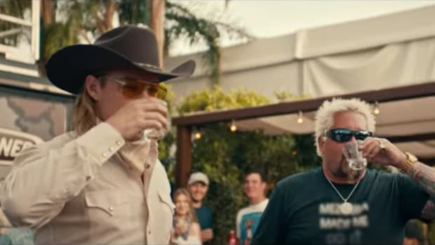 "A screen capture of Diplo (real name Thomas Wesley Pentz Jr.) and Guy Fieri doing shots in the music video for Diplo's country-inspired single ""So Long."""