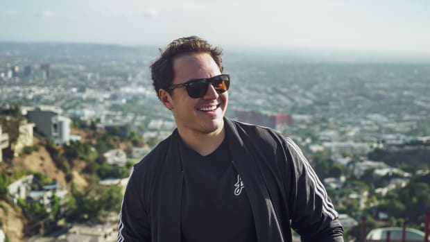 A photo of DJ/producer Lo Key wearing sunglasses in front of a scenic view.